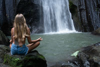 Aerial drone view back of woman meditating at the beautiful waterfall in green tropical rain forest in Bali