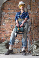 young woman in work clothes with a protective helmet and a heavy hammer drill stands near a brick