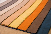 Colorful and bright fabric samples of leatherette furniture and clothing upholstery. Close-up of a palette of textile abstract stripes of different colors