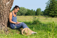 Woman sits against tree writing in meadow