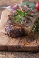 Gegrilltes Steak auf Holz mit Gewürzen