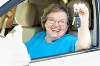 Happy Senior Woman Sitting In New Car Holding The Keys