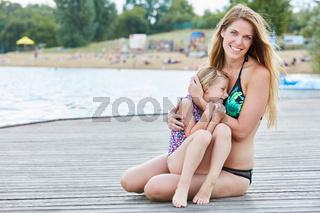 Mädchen kuschelt sich in die Arme der Mutter