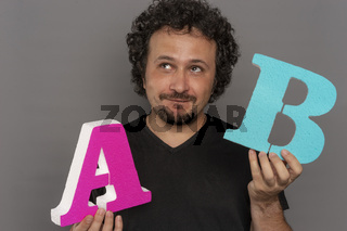conversion funnel, A / B test in marketing and online advertising. Brunette man holding colored letters A and B in hands with face expressions
