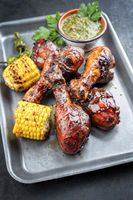 Traditional barbecue chicken drumsticks with corn and chimichurri sauce as top view in a silber fryer