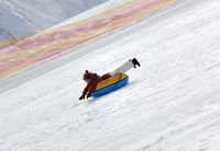Young girl downhill on snow tube on ski resort at sunny day in snowy mountains