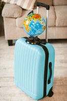 Close up view of bright suitcase with globe.