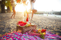 Happy slim tan women are dancing on the beach in sunset. Travel and happiness concept