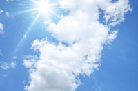 blue sky with bright sun and white clouds