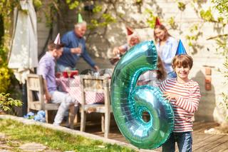 Geburtstagskind mit Luftballon in Form einer Sechs