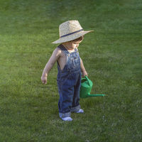 Family, little gardener in a garden of a house with a small green watering can watering the plants, wearing a cowboy breastplate and a straw hat