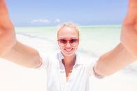 Young woman wearing white beach tunic taking selfie on tropical white sandy beach.