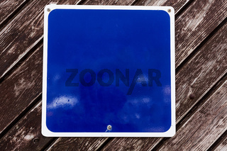 Empty blue board with copy space above wooden background. Advertising concept with empty blue copy space.