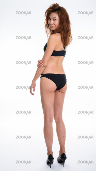 Full body shot of back view of young Asian woman looking at came