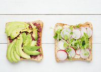 Two avocado toasts on white wooden background