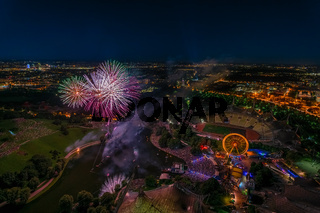 Aerial panoramic cityscape view with bright fireworks lights in night Munich.