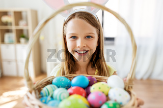 happy girl with colored easter eggs at home