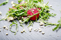 Beetroot arugula and feta cheese salad on slate stone plate closeup view