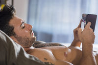 Shirtless muscular man in bed typing on cell phone