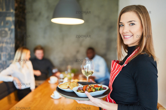 Freundliche Kellnerin serviert Vorspeisen