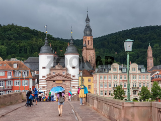 People stroll on the Old Bridge in the beautiful medieval city of Heidelberg in Germany
