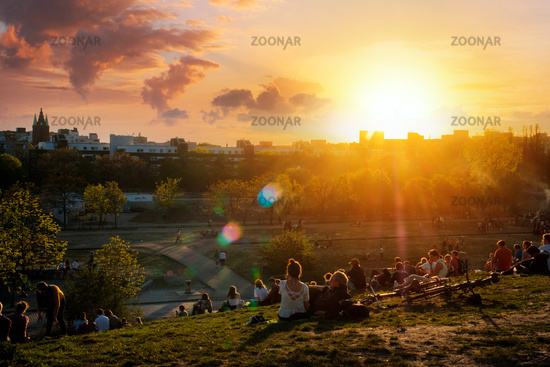 People enjoying view on sunset sky over skyline from public park (Mauerpark) on summer day in Berlin