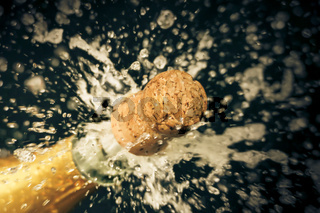 a champagne cork is popping out