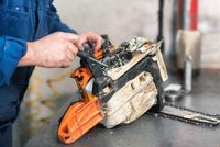 Mechanic repairing a chainsaw. Man repairing a chainsaw in workbench.
