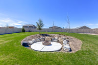 Circular fire pit surrounded by rocks in the middle of the grassy yard of a home