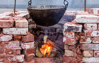 hanging big black sooty cauldron over  bonfire surrounded by a brick wall
