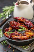 Baked pork ribs in honey glaze with rosemary and cherry sauce.
