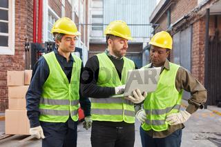 Drei Logistik Arbeiter mit Laptop Computer