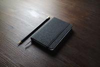 Black notebook, pencil