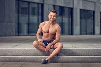 Muscular shirtless man sitting on urban steps