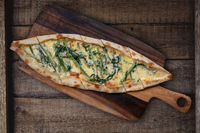Turkish pide with morning glory and cheese on rustic wooden table