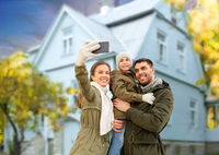 family taking selfie by smartphone house in autumn