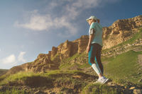 Attractive sports girl in a cap and headphones before jogging in a picturesque location next to the rocks at sunset. Workout outdoors. Back view