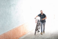 hipster man with a backpack pushing a retro bicycle