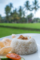Steamed rice with prawn crackers and vegetables on white plate over blurred rice fields