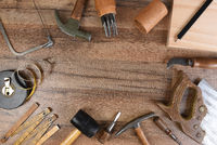 High angle closeup of a large group of tools arranged on a wood workbench around a blank space in th