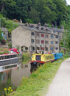 the rochdale canal running through hebden bridge with moored boats reflected in the water and stone buildings surrounded by trees