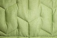 Close-up comfortable green soft sofa with curly stitching. Modern design