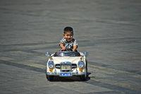 4 bis 6jähriger Junge fährt in einem elektrisch betriebenen Spielzeugauto auf dem Dschingis Khan-Platz