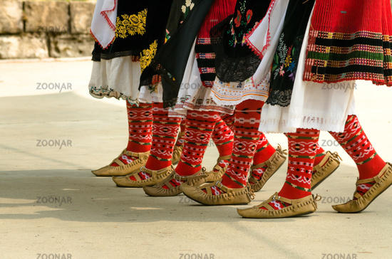 Girls dancing folk dance. People in traditional costumes dance Bulgarian folk dances. Close-up of fe