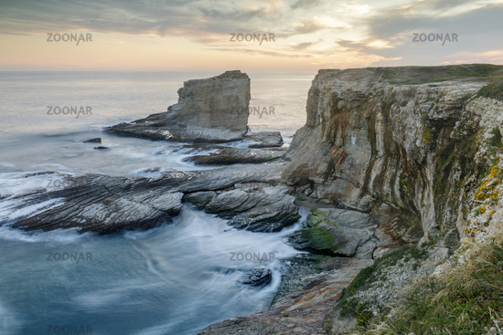 Sunset over rocky coastline near Panther and Hole-In-The-Wall Beaches.