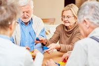 Senioren Gruppe spielt mit bunten Bausteinen