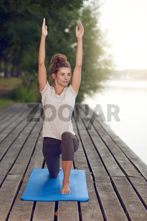 Active slender young woman exercising outdoors