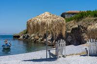 Deckchair and an umbrella made of straw on a stony beach. Summer landscape