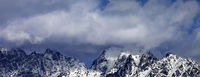 High snowy mountains in clouds at sunny day