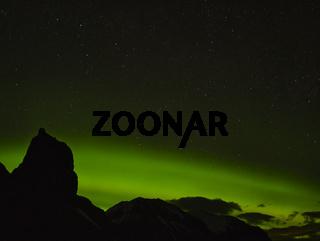 Aurora Borealis hinter einer Bergkette in Island